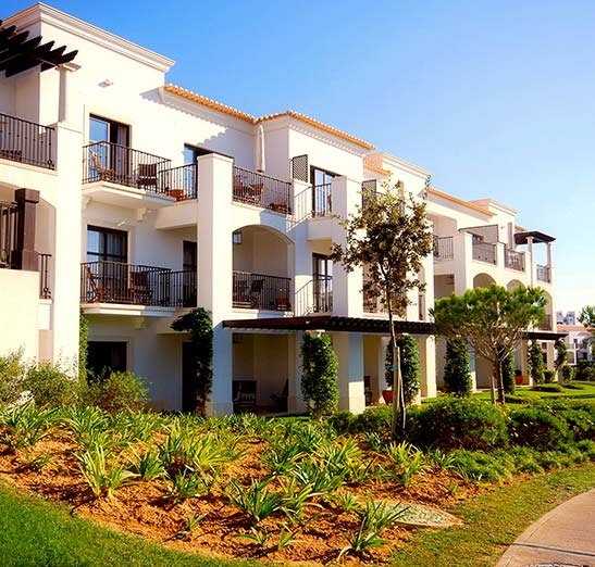 Spanish style apartments or condo with lush landscaping and blue sunny skies. White stucco walls with terracotta roof tiles.