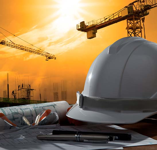Construction graphic with cranes, hardhat, blueprints, pens, protective googles, standing steel and workers in the background