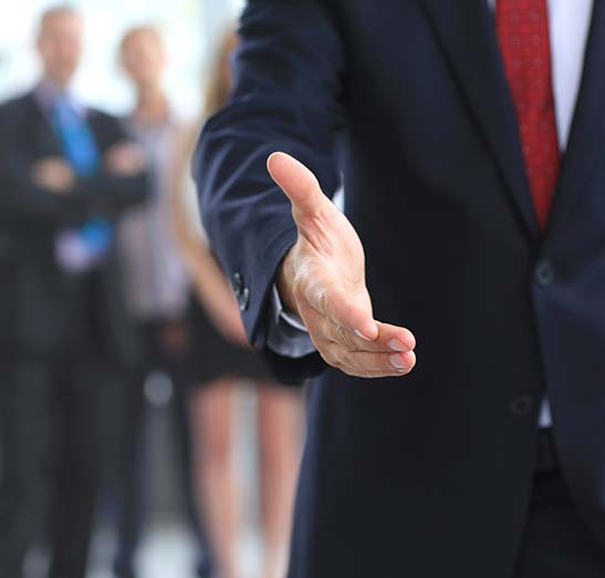 Business man dressed in a suit and tie extending his hand to shake hands.
