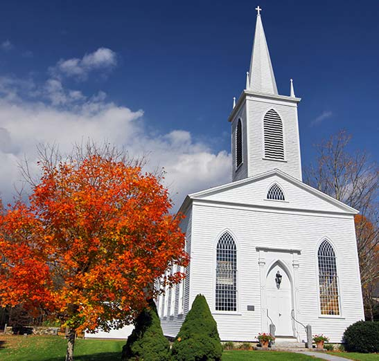 Beautiful small white classic brick church with colorful trees.
