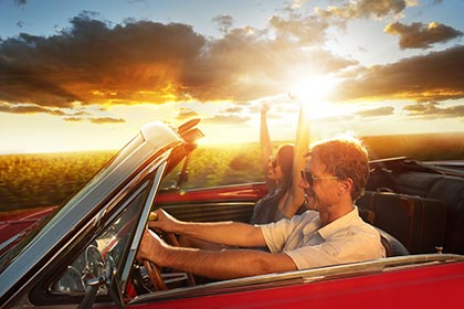 Happy couple driving in an antique auto with the top down. Red classic sports car at sunset. Smiling man driving and excited woman with hands raised in joy.