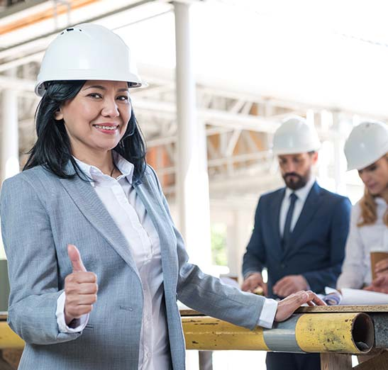 Outdoor photo of a construction job site with female contractor in the foreground smiling giving a thumbs up to the camera while a business man and woman review blueprints drinking coffee. All three are wearing construction hard hats and dressed in business professional attire.