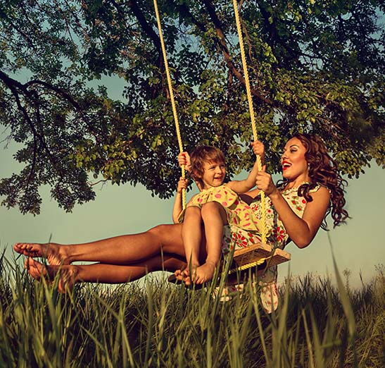Mother swinging from tree swing holding her daughter in her lap. Beautiful sunset, summer time photo.