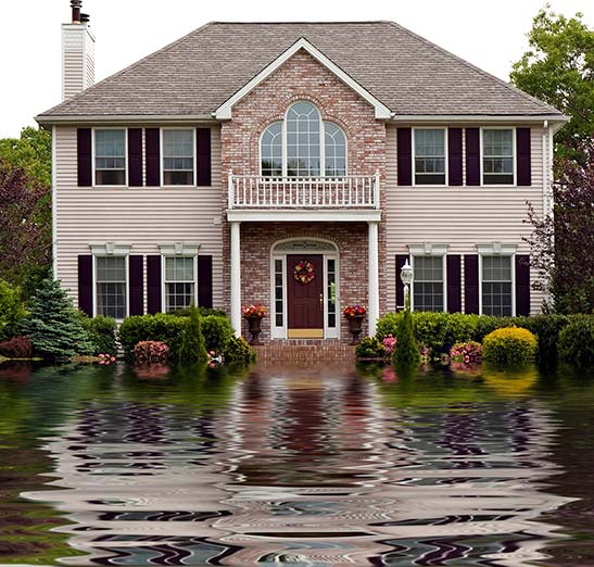 Flooded residential yard with two story home shown in the background. Call Odiorne today if you need a flooding insurance quote.