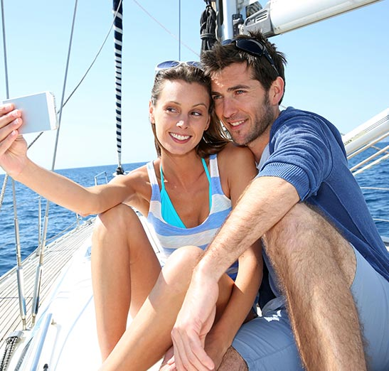 Happy couple sailing and taking selfie while out on the water.