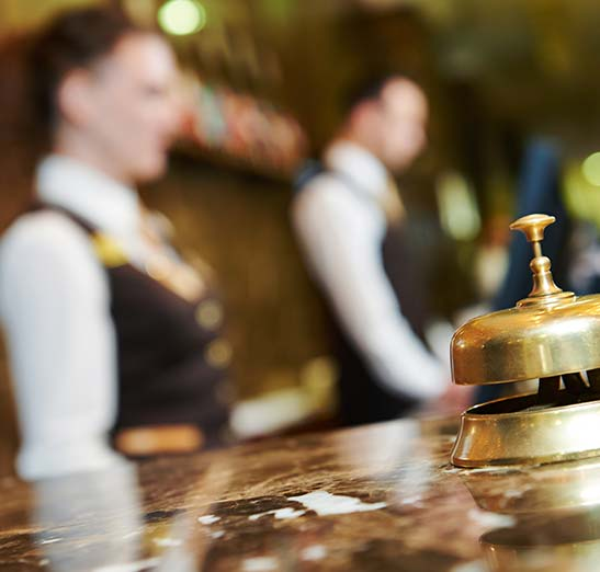 Hotel workers shown out of focus in background with a brass bell on a marble counter shown in focus in the foreground.