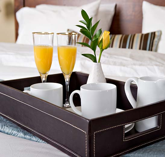 Hotel bed with decorative serving tray sitting with coffee and orange juice in champaign glasses and a vase with a single yellow rose with greenery. The china is all white and classy. The bed is adorned in fine linen bedding.