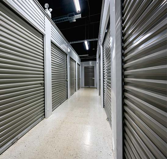 Interior self storage garage units looking down a long internal hallway of self storage rooms.