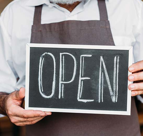 Business owner holding an open sign.