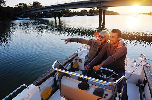 Happy couple out on a motor boat on the river at sunset. For motor boat insurance contact Odiorne Insurance today.