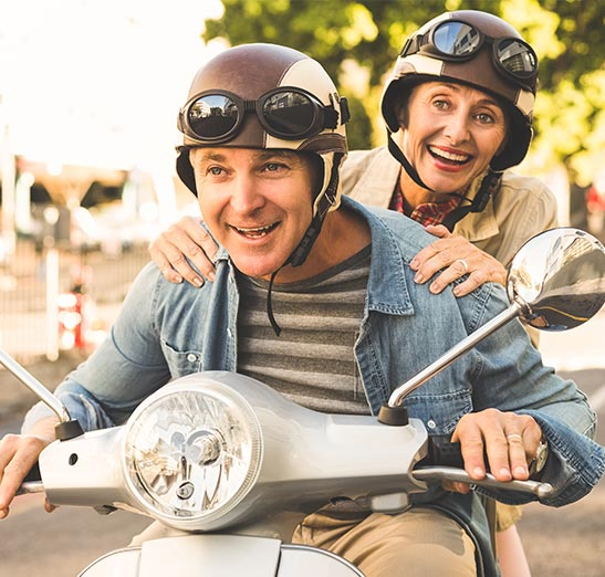 retirement planning - happy retired couple riding a moped with helmets and funny googles enjoying a ride through the city. The older man is driving with his wife smiling a hanging on to his shoulders riding behind him.