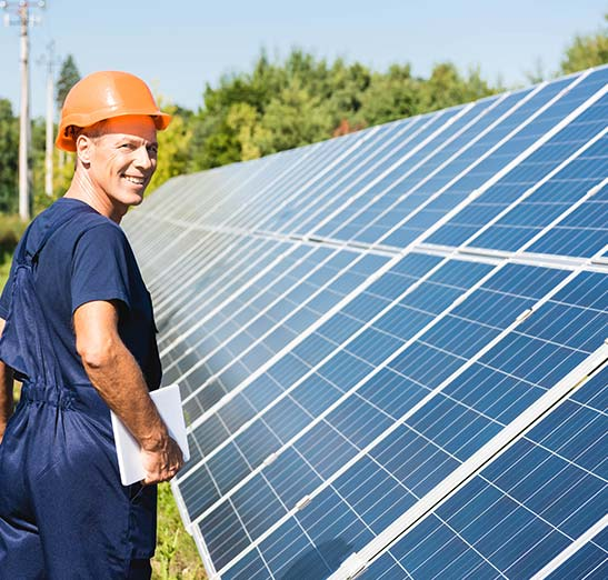 Worker inspecting solar array. Smiling and wearing jumpsuit wearing orange hardhat. Beautiful sunny day and green trees.