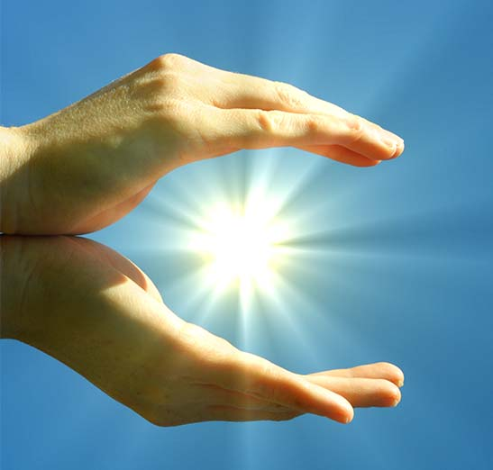 Solar Energy Graphic: Sun shining through cupped hands with blue sky background.