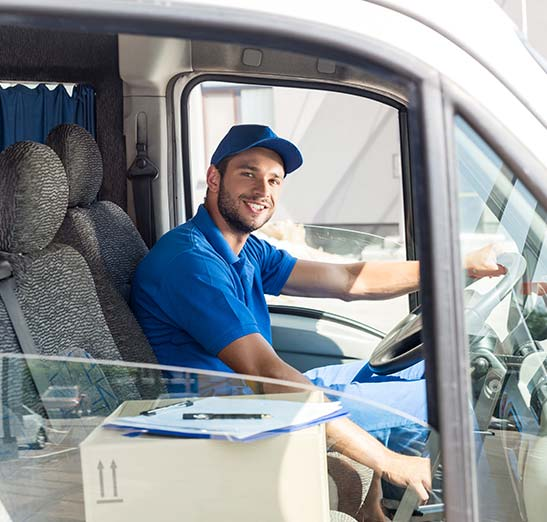 Deliver driver smiling from deliver van with boxes shown in the passenger seat.