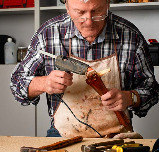 Older wood working crafter hot glueing a piece of wooden furniture.